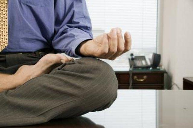Businessman meditating barefoot on desk