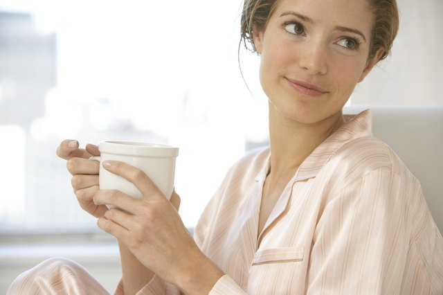 Young woman wearing pyjamas, holding cup, looking to side