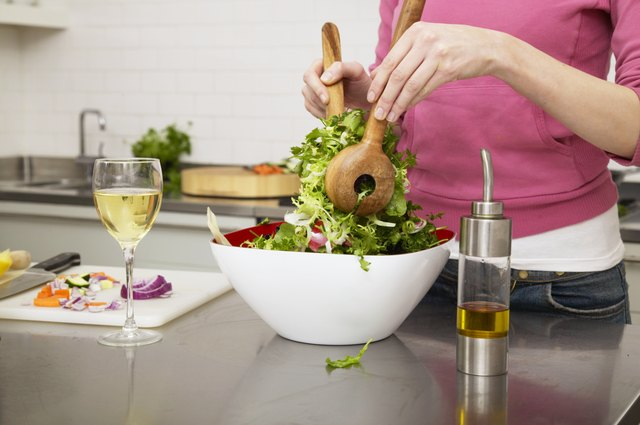 Young woman preparing salad in kitchen, mid section