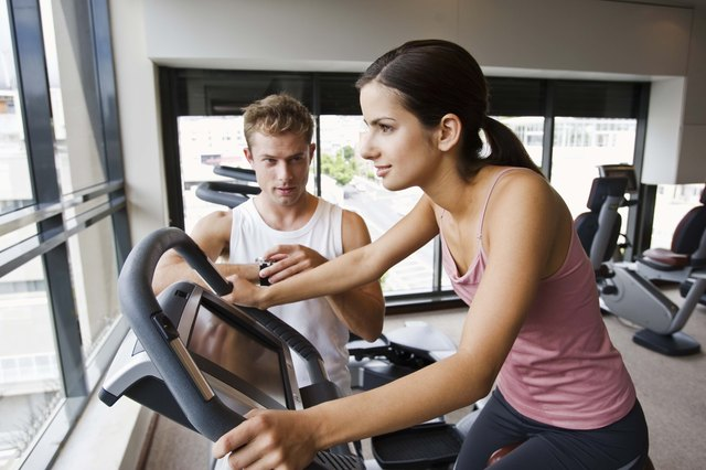 Man watching woman on exercise bike at gym