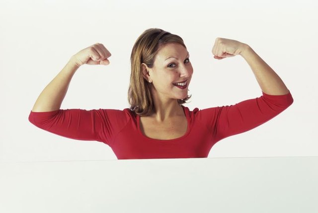 Portrait of a young woman flexing her biceps
