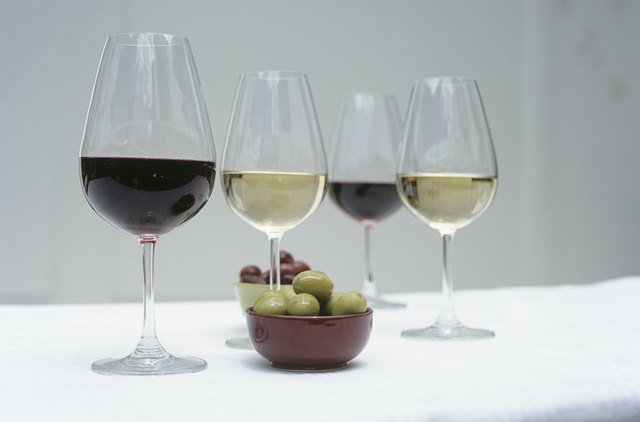 Glasses of wine and olives on table