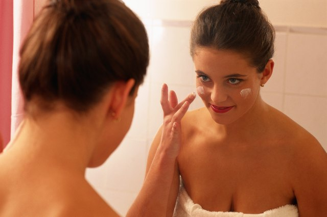 Woman standing in front of mirror, applying face cream