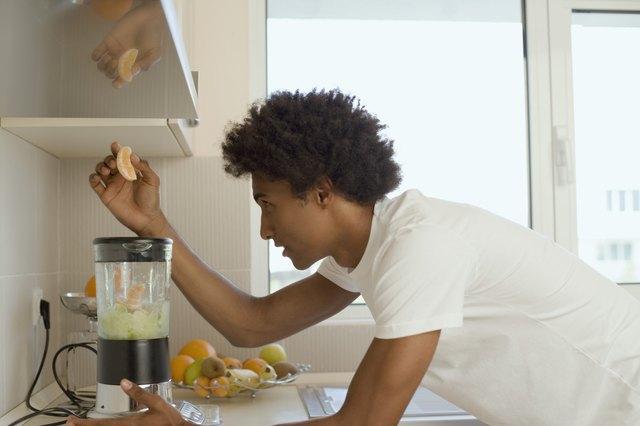 Man putting fruit in blender