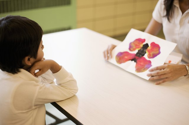 Teacher showing inkblot paintings to student