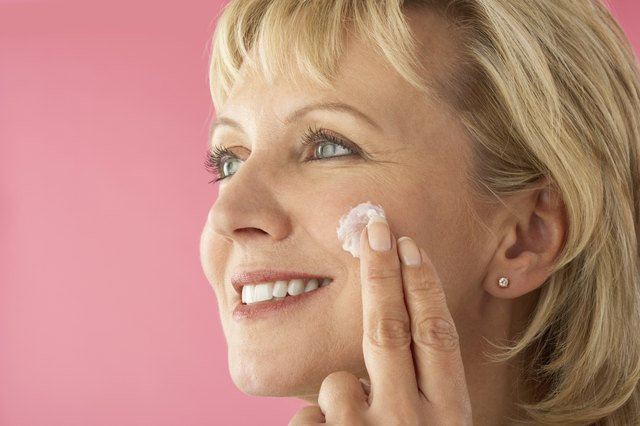 Woman Putting On Facial Cream