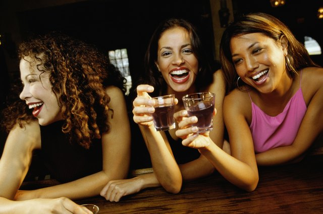 Three young women toasting with glasses in a bar