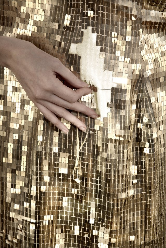 Gold sequin dress being mended
