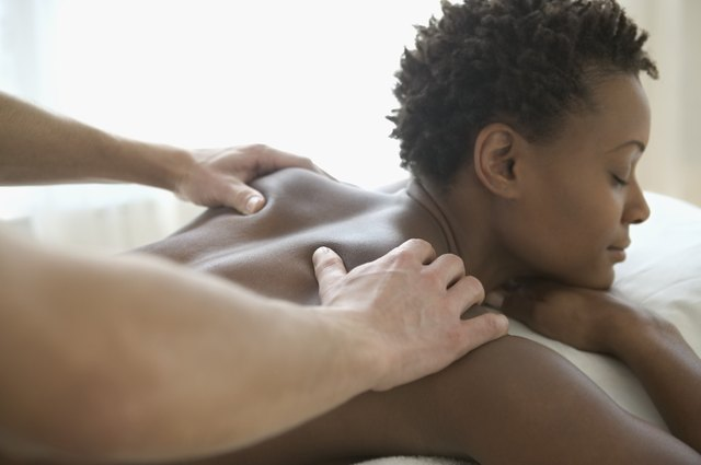 Rear view of a young woman getting a back massage