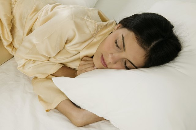 High angle view of a young woman sleeping on a bed