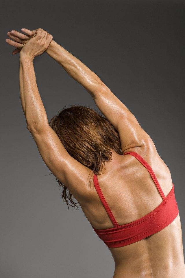 Female athlete stretching, rear view, studio shot