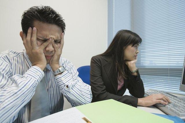 Frustrated Asian businessman at desk
