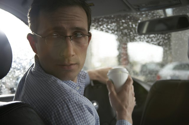 Man drinking coffee while driving car, looking over shoulder