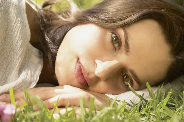 Young woman lying on the grass looking at camera