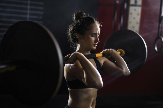 Strong woman holding heavy weight on her shoulders