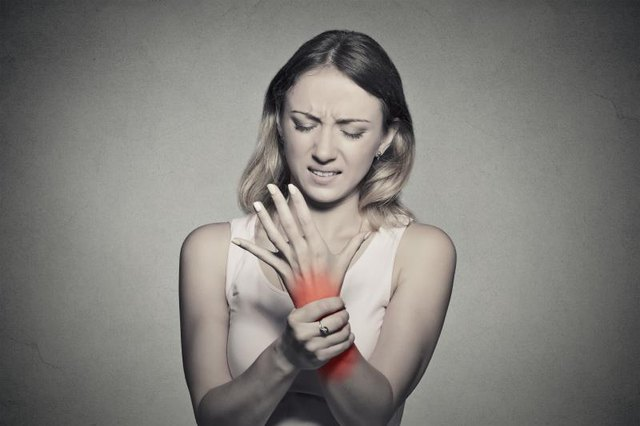 Young woman holding her painful wrist isolated on gray wall background. Sprain pain location indicated by red spot. Negative face expression .