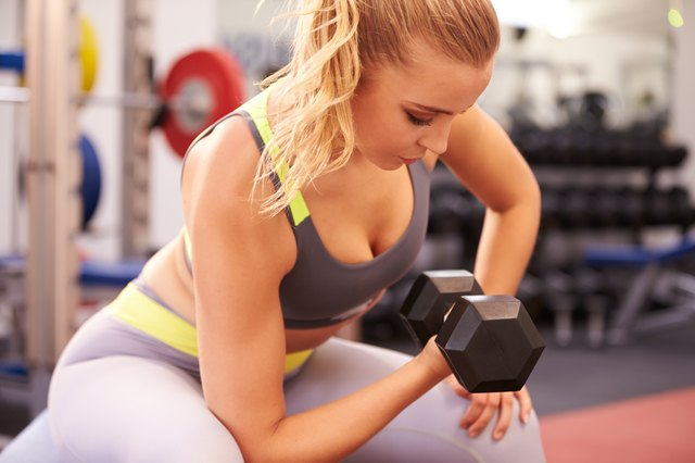 Young woman exercising with dumbbells at a gym, horizontal