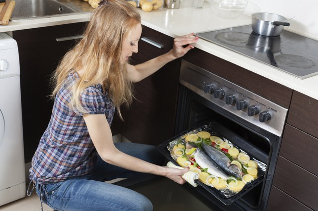 Ordinary girl cooking raw fish in oven