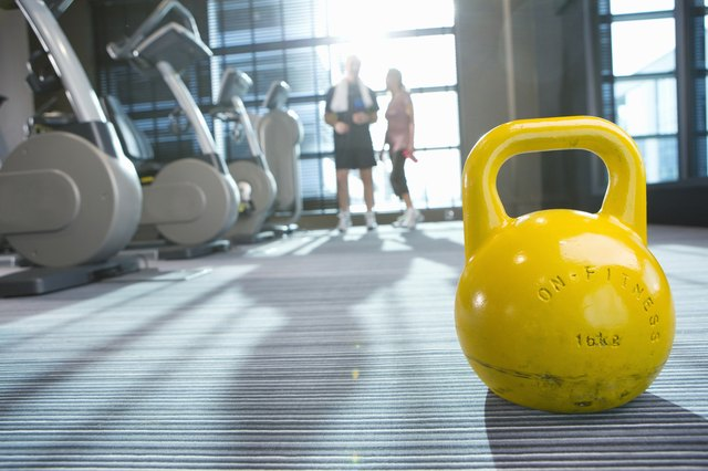 Yellow medicine ball on floor in health club with couple