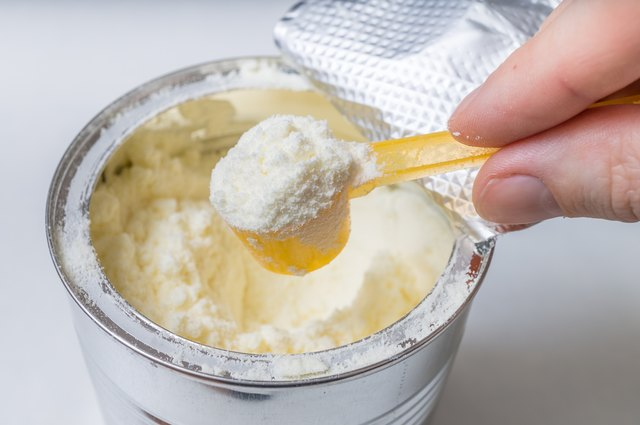 Hand holds scoop with newborn milk formula.