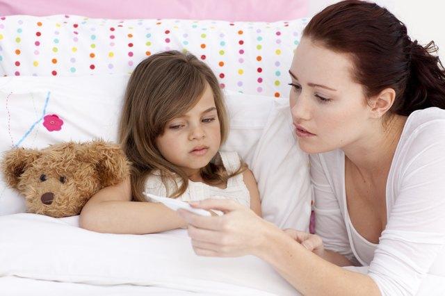 Mother taking sick daughter's temperature
