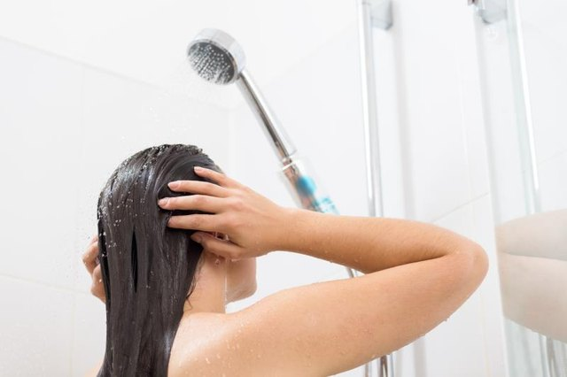 Shot of a young woman washing her hair in a shower