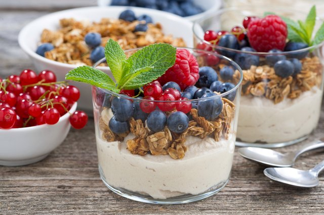 dessert with sweet cream, fresh berries and granola, closeup
