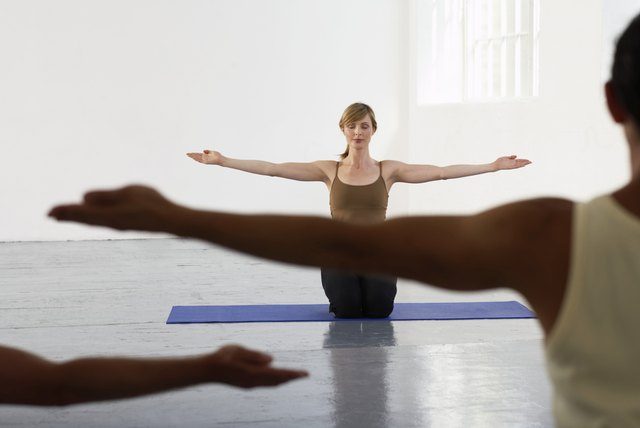 Yoga teacher kneeling at front of class, arms outstretched, eyes closed