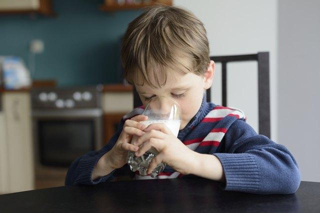 preschooler politely drinking milk at the table
