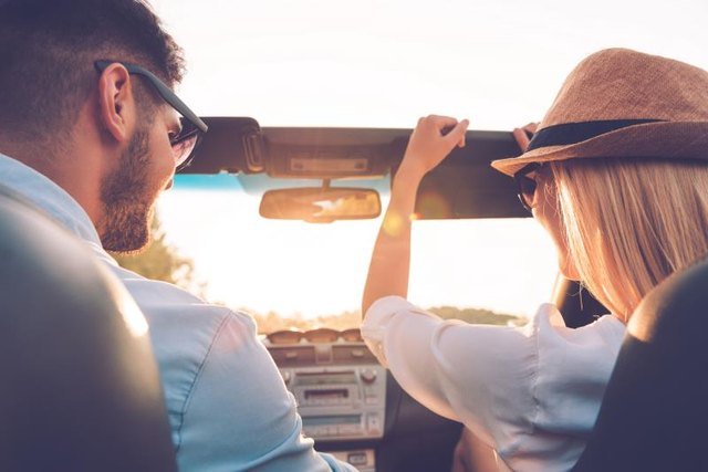 Rear view of joyful young couple having fun while riding in their convertible
