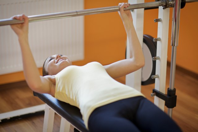 Young woman lift a barbell on a bench