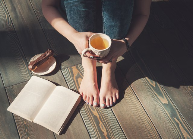 Cozy photo of young woman with tea and book