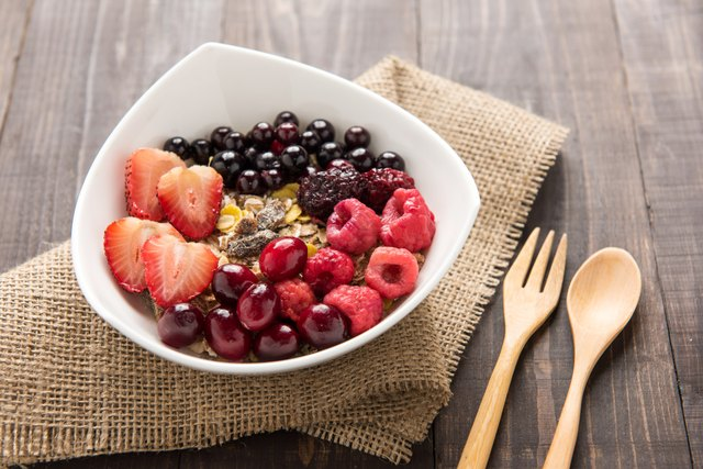 Oatmeal in bowl topped with fresh blueberries, cranberries, stra