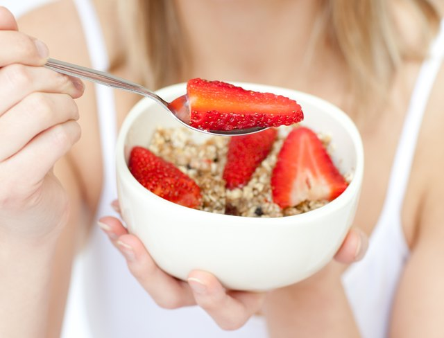 Close-up of a woman eating cereals with strawberries