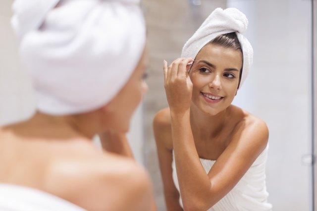 Happy young woman tweezing eyebrows