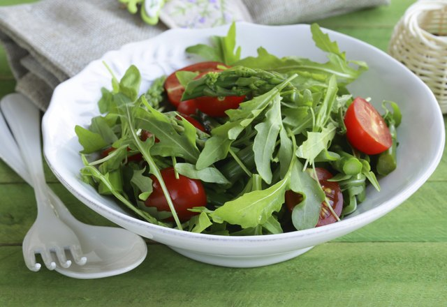 salad with arugula and tomatoes served on a wooden table
