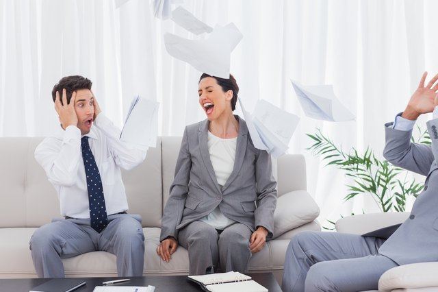 Businessmen shocked at colleague screaming and throwing papers