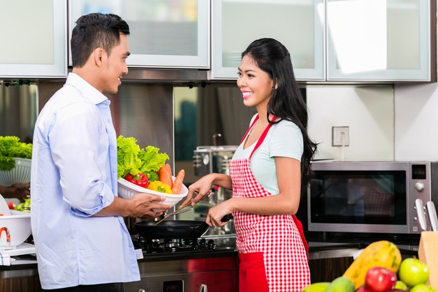 Asian couple cooking food together in kitchen