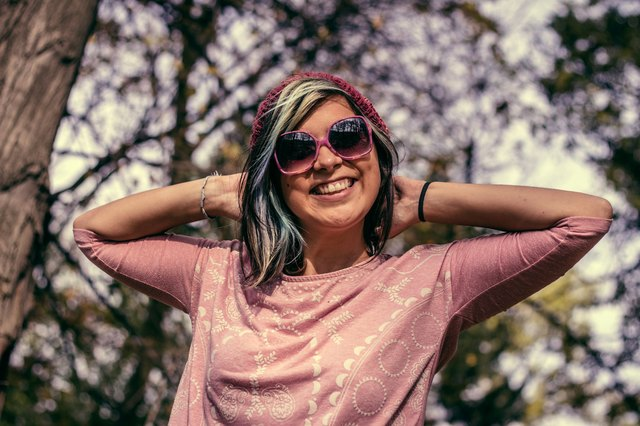 Young cute hipster woman with sunglasses and hat smiling