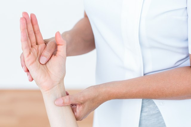 Physiotherapist examining her patients hand