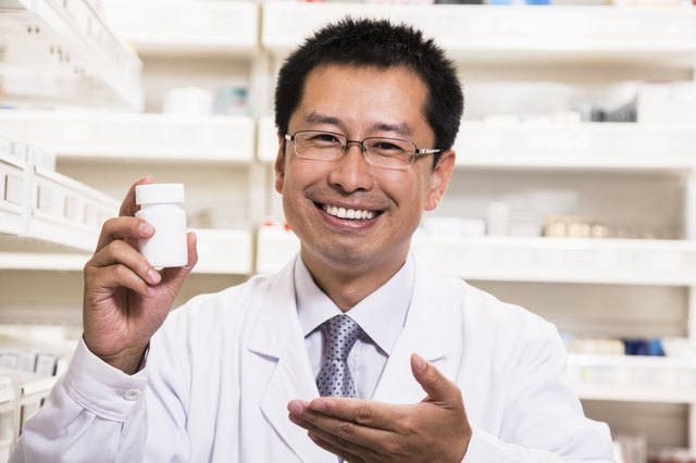Portrait of smiling pharmacist holding a prescription medication bottle in his hand