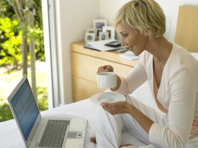 Woman sitting on bed holding cup and saucer, looking at laptop