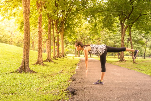 Woman runner stretching warm up with single-leg deadlift before running.