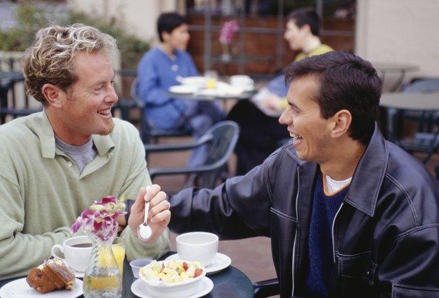 Men eating breakfast at outdoor cafe