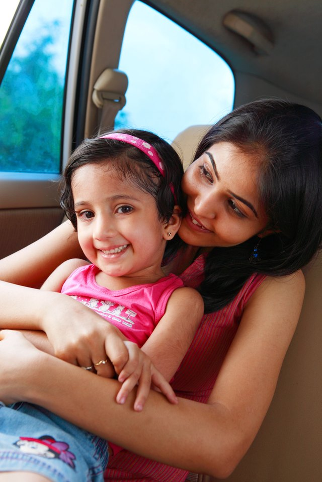 Girl sitting with her mother in a car