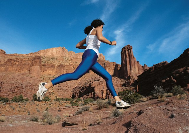 woman running across the desert in a blue spandex outfit at Fisher Towers in Moab Utah