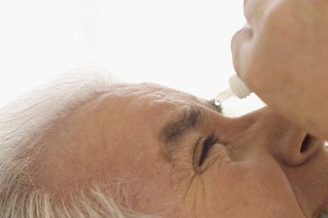 Smiling mature man applying eye drops into eye, extreme close-up
