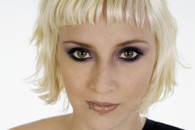 Young woman with bleached blonde hair and face piercings, close-up