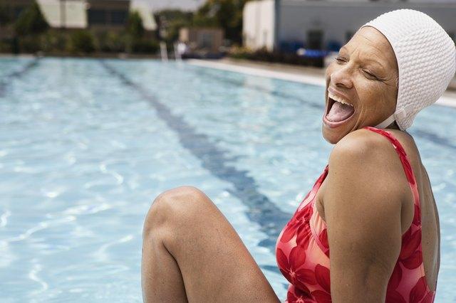 Laughing senior woman swimmer at pool