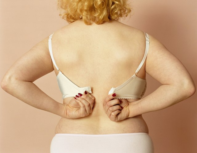 Young woman putting on bra, mid section, rear view